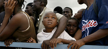 A boy watches a passing helicopter as Haitians line up to receive high-protein biscuits being handed out by the World Food Program with the assistance of United Nations troops. (photo-caption: Carolyn Cole, LA Times)
