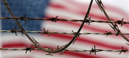 An American flag behind barbed wire, and all that implies, 06/15/09. (photo: public domain)