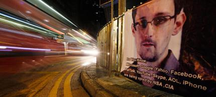 A bus drives past a banner supporting Edward Snowden in Hong Kong's business district, 06/17/13. (photo: Kin Cheung/AP)