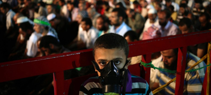 A boy wears a tear gas mask as supporters of Egypt's ousted President Mohammed Morsy pray at the camp set up by supporters in the Nasr City area of Cairo on July 28. (photo: CNN)