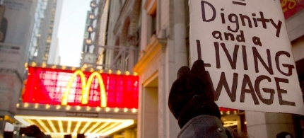 A protester holds up a sign at a demonstration outside McDonald's in Times Square in support of employees on strike at various fast-food chains in New York, 11/29/12. (photo: Reuters/Andrew Kelly)