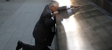 Robert Peraza kneels by his son's name on the 9/11 memorial wall. (photo: Justin Lane/AP)
