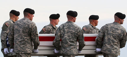 Soldiers carry a flag draped coffin of a fallen comrade. (photo: AP)