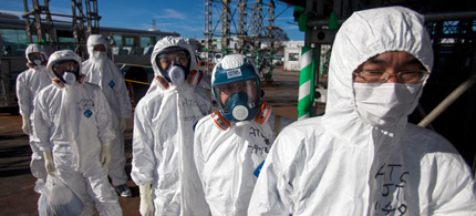 Workers in protective suits and masks wait to enter the emergency operation center at the crippled Fukushima Dai-ichi nuclear power station. (photo: AP)