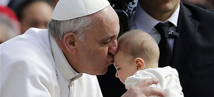Pope Francis kisses a baby handed to him as he is driven through the crowd in St. Peter's Square. (photo: AP)