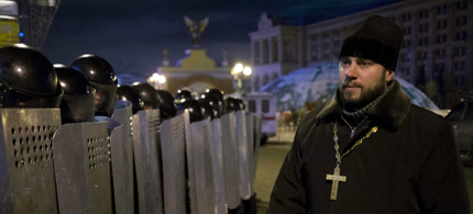 A Ukrainian priest walking past riot police. (photo AP)