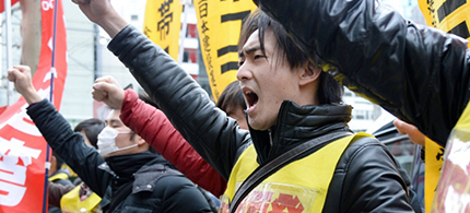Fukushima nuclear workers and their supporters shouts slogans as they raise their fists in front of the headquarters of Tokyo Electric Power Company (TEPCO), operator of the tsunami-battered Fukushima Daiichi nuclear power plant, during a rally in Tokyo on March 14, 2014. (photo: Toru Yamanaka/AFP/Getty Images)