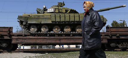 A woman walks past a train loaded with Ukrainian tanks. (photo: Max Vetrov/AFP)