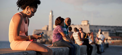 A woman uses her cellphone as she sits on the Malecon in Havana, Cuba. (photo: Franklin Reyes/AP)