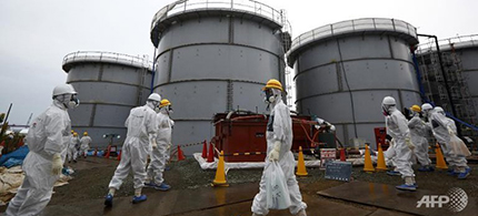 Members of the media and Tokyo Electric Power Co employees walk past storage tanks for radioactive water in the H4 area at the Fukushima Dai-ichi nuclear power plant in Japan. (photo: AFP/Tomohiro Ohsumi)