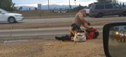 California Highway Patrol officer beating homeless woman. (photo: AP/David Diaz)