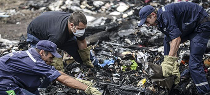 Ukrainian State Emergency Service employees search for bodies among the wreckage at the crash site of Malaysia Airlines Flight 17. (photo: Bulent Kilic/AFP/Getty Images)