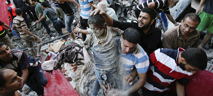 Palestinians evacuate a survivor of an Israeli airstrike that hit a family building Sunday in Gaza. (photo: AP/Eyad Baba)
