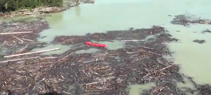 Aerial footage shows the debris and milky blue-green tailings pond water that washed into nearby waterways after the Mount Polley Mine tailings pond breached Monday, Aug. 4, 2014. (photo: Cariboo Regional District/Facebook)