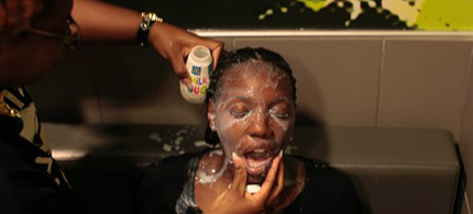 A woman has her face doused with milk after suffering the effects of tear gas used by police in Ferguson. (photo: Joshua Lott/Getty Images)