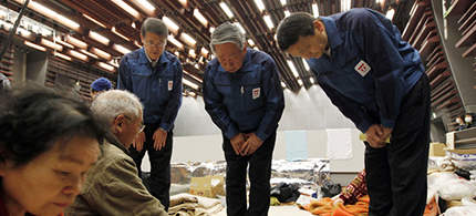 TEPCO executives bow their heads to apologize to evacuees at a shelter in Koriyama. Will any face criminal prosecution? (photo: Ken Shimizu/AFP/Getty Images)