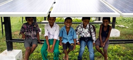 Youths pose under a solar panel. (photo: Greenpeace)