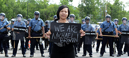 A woman holds a sign reading 'We are Michael Brown' in Ferguson amid police presence. (photo: David Broome/UPI)