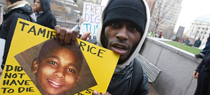 A protester holds a poster picturing shooting victim Tamir Rice, during a rally at Public Square in Cleveland, Ohio, on Monday. (photo: David Maxwell/EPA)