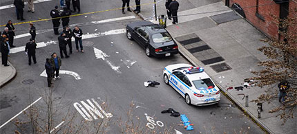 12/20/14 - Police officers look on near the scene where NYPD patrolman were killed ay a gunman. (photo: TheSource.com)