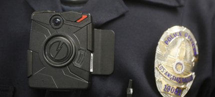 A police officer wears an on-body camera. (photo: Damian Dovarganes/AP)