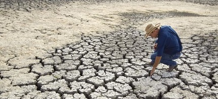 A man inspects a dried lake in Texas. (photo: Austin Statesman)