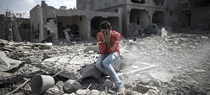 A Palestinian man cries in front of his destroyed house in northern Gaza Strip. (photo: Oliver Weiken/EPA)