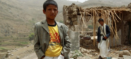 A Yemeni boy stands in front of a damaged house hit by a Saudi coalition airstrike. (Photo: Mohammed Huwais/AFP/Getty Images)