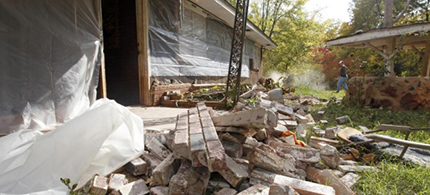 A man works to clear up bricks that fell from his in-laws' home in Oklahoma in 2011. Earthquake frequency rose from 20 in 2009 to 585 in 2014. (photo: Sue Ogrocki/AP)
