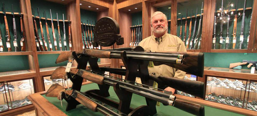 Outfitter Paul Harris stands behind a shotgun display in the gun library of a new Cabela's store in Anchorage, Alaska, Thursday, March 27, 2014. (photo: Dan Joling/AP)