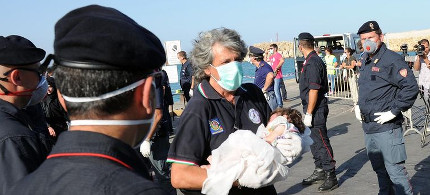 An Italian rescue worker carries a refugee baby saved off the coast of Italy earlier this summer. Photos like this are a reminder that Aylan Kurdi's death was sadly predictable: we already knew that children were making the dangerous crossing. (photo: Giovanni Isolino/AFP/Getty)