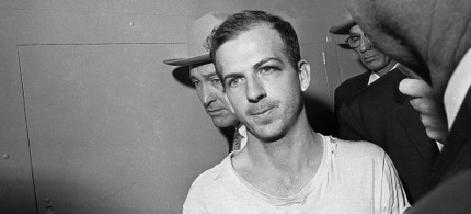 In this Nov. 23, 1963 file photo, Lee Harvey Oswald is led down a corridor of the Dallas police station for another round of questioning in connection with the assassination of U.S. President John F. Kennedy. Oswald, who denied any involvement in the shooting, was formally charged with murder. (photo: AP)