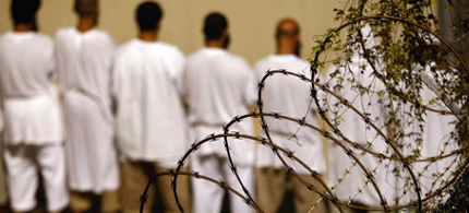 Detainees stand during an early morning Islamic prayer at the U.S. military prison for 'enemy combatants' in Guantanamo Bay, Cuba. (photo: John Moore/Getty Images)