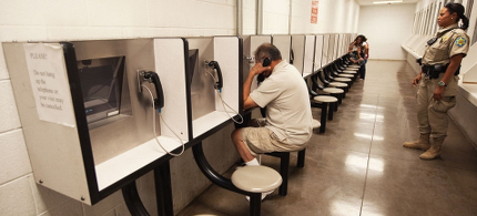 Detention Officer Rene Ansley, right, supervising visitors using videophones to speak with inmates at the Maricopa County tent-city jail in Phoenix, Arizona, in 2010. (photo: Paul J. Richards/AFP/Getty)