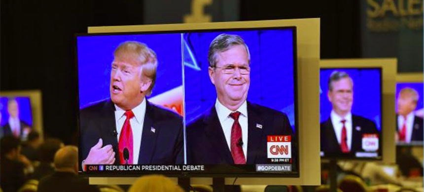 Republican U.S. presidential candidates businessman Donald Trump (L) and former Governor Jeb Bush (R) are seen debating on video monitors in the debate press room during the Republican presidential debate in Las Vegas, Nevada, December 15, 2015. (photo: David Becker/Reuters)