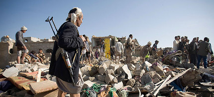 A Houthi Shiite fighter stands guard on Thursday as people search for survivors under the rubble of houses destroyed by Saudi airstrikes near Sanaa Airport. (photo: AP)