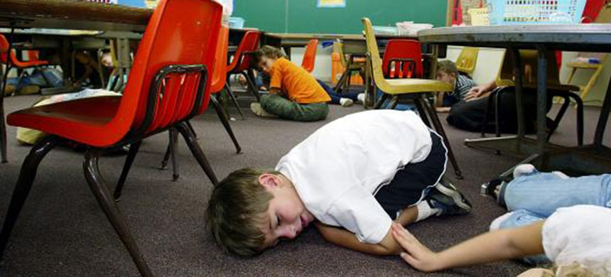Kindergarten students lie on the floor during a classroom lockdown drill in Oahu, Hawaii. (photo: Phil Mislinski/Getty Images)