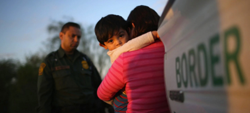 A one-year-old from El Salvador clings to his mother after she turned themselves in to Border Patrol agents on December 7, 2015, near Rio Grande City, Texas. (photo: John Moore/Getty Images)
