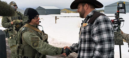 Ammon Bundy, right, shakes hand with a federal agent guarding the gate at the Burns Municipal Airport in Oregon on Friday, Jan. 22, 2016. (photo: Keith Ridler/AP)