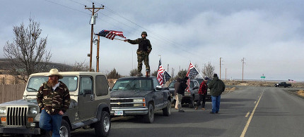 Thomas Wagner waved a flag near the Malheur National Wildlife Refuge on Thursday. (photo: Rebecca Boone/AP)