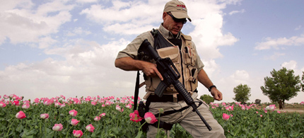 A private security contractor walks in a poppy field. (photo: John Moore/Getty Images)