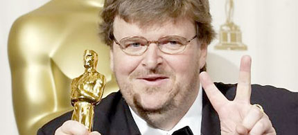 Michael Moore flashes the peace sign as he holds his Oscar for Best Documentary Feature at the 2003 Academy Awards, 03/07/03 (photo: Reuters)