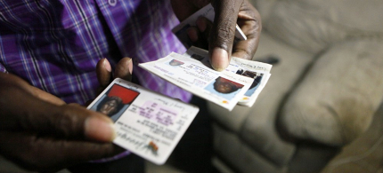 A voter holds various ID cards. (photo: Jaime Henry-White/AP)