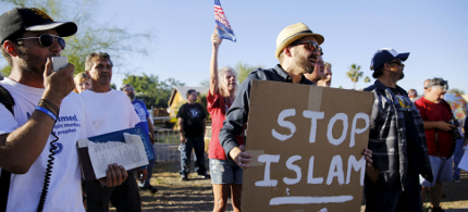 A demonstrator shouts and carries a 'Stop Islam' sign while another rips pages out of a Quran during a 'Freedom of Speech Rally Round II' outside the Islamic Community Center of Phoenix, Arizona. (photo: Nancy Wiechec/Reuters)