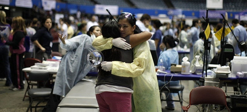 A woman hugs a doctor after her dental treatment at the Care Harbor/LA free clinic in Los Angeles. (photo: AP)