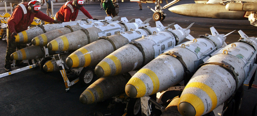 Aviation ordinancemen organize 1000 pound MK-83 JDAM (Joint Direct Attack Munition) bombs on their racks on the flight deck of the USS Kitty Hawk aircraft carrier. (photo: Paul Hanna/Reuters)