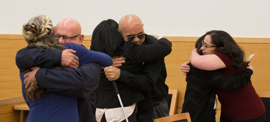 Amaury Villalobos and William Vasquez reacted after their exonerations in a 1980 Brooklyn arson case. From left, Adele Bernhard, a lawyer, with Mr. Villalobos; Rita Dave, a lawyer, with Mr. Vasquez; and the widow of Raymond Mora, a third defendant who was cleared, Janet Mora, and their daughter, Eileen Mora. (photo: Pearl Gabel/NYT)