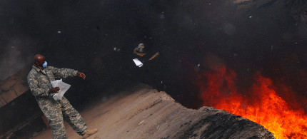 US soldier works near a burn pit. (photo: Reuters)