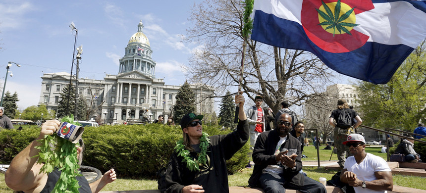 A man waves a Colorado flag with a marijuana leaf on it at Denver's annual 4/20 marijuana rally in front of the state capitol building in downtown Denver, April 20, 2015. (photo: Rick Wilking/Reuters)