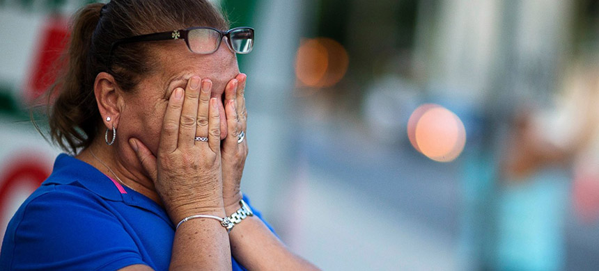Carmen Feldman, of Orlando, cries while visiting for the first the scene of the Pulse nightclub mass shooting from a block away Friday, June 17, 2016, in Orlando, Florida. (photo: David Goldman/AP)